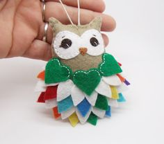 This cutesy little owl was all hand stitched, embroidered, and appliqued featuring individually hand cut feathers in shades of the rainbow with 3 green heart shaped feathers on a light taupe body. A tiny heart and the year 2017 are hand stamped on an aluminum tag that adorns the back of the owl.  Lightly stuffed with poly-fill and finished with a loop of cotton cord for hanging.  Measures approximately 3 3/4 long by 2 1/2 wide, not including hanger.  This owl is ready to ship, and w...