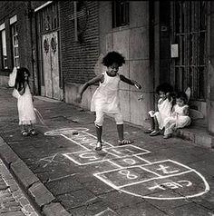 """A amarelinha é uma das brincadeiras de rua mais tradicionais do Brasil e conhecida internacionalmente. Percorrer uma trajetória de quadrados riscados no chão de pulo em pulo tinha diversos nomes. Eu conhecia como """"macaquinho"""". Usava um """"caquinho"""" de cimento ou uma """"casquinha de banana"""" dobrada...hehe.... Hoje, em tempos de jogos eletrônicos, internet e televisão, surpreendentemente a brincadeira simples ainda sobrevive firme e forte nos hábitos de milhões de crianças."""