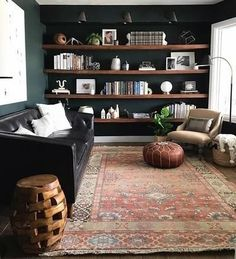 Great dark walls behind open book shelves in modern living room. Love the floor lamp and sofa