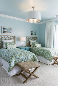 Whereas the Winterberry model home's living room showcases light ocean blues and sandy whites, the guest bedroom focuses on vibrant tropical greens. Paisley linens are reinvented to work within this coastal design theme – and brilliantly, we might add! Interior design by Susan J. Bleda and Amanda Atkins, Robb & Stucky