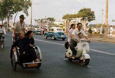 1960's in Saigon, Vietnam, along the Bach-Dang Quay at Catinat street. (Photographer: Wilburg)  Cuộc sống người Sài Gòn những năm 60 - Người đàn ông chở vợ và con trai dạo phố trên chiếc xe Vespa màu trắng bên cạnh hai bà cụ đi xích lô ngắm phố phường. Ảnh chụp ở bến Bạch Đằng năm 1961.
