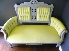 A 19th century Eastlake tufted walnut settee. Supported on casters. Enhanced with a distressed silver finish, this masterfully crafted chair has been giving new life in yellow velvet upholstery, silver nail head treatment, and contrasting black and white gimp trim. Victorian style, by restyledbyvalerie.