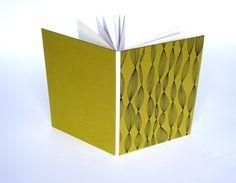 Mit seiner sichtbaren Heftung ist das Buch bestimmt in jedem Bücherregal ein Hingucker. Die Buchdeckel sind mit einem kräftigen grüngelblichen Papier