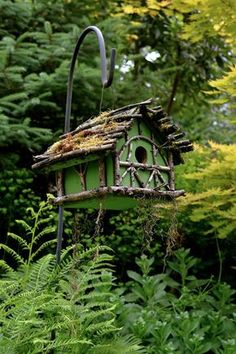 A simple wooden birdhouse, with paint, sticks and moss added. Charming!