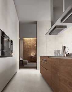 Euorpean kitchen [Varenna by Poliform] Sophisticated palette of materials [travertine + timber veneer + paint + stainless steel]  The lighting the room beyond really leads you through and you almost know it is going to be a calm / sophisticated almost insulated space.