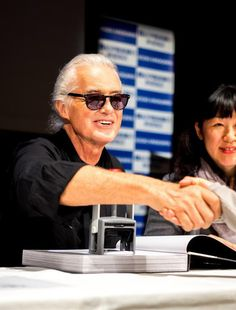 Jimmy Page shakes hand with a fan at the signing of his book at Kinokuniya Bookstore, Tokyo, October 9, 2014.