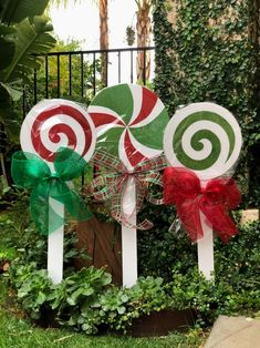 Holy lollipops! These beautiful lollipops are sold as a set of three for $75. They stand 36 inches tall and are made on a PVC circle cut out, paint and glitter and on a wooden painted stake and sealed with a mesh bow. The large multi colored lollipop is 14 inch and you also will receive 2 -12 inch lollipops (one red and one green swirl lollipops) **please note: the gingerbreads in the pictures are NOT INCLUDED in this listing. They are also available. Please click on the link to order .. Gingerbread Christmas Decor, Candy Land Christmas, Christmas Wood, Christmas Projects, Diy Christmas Yard Art, Exterior Christmas Lights, Christmas Float Ideas, Grinch Decorations, Outside Christmas Decorations