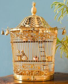 applied with borders of scrolling foliage and with a matching door latch, the pagoda-style top hung with bells and with pineapple finial, the wood base with two pull-out trays,the interior with two feeders, two wood perches, one ladder with wood rungs, and six birds
