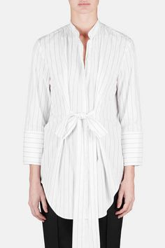 The white shirt gets a feminine twist with an attached front tie that accents the waist of this crisp yet fluid tunic. Pinstriped cotton shirting puts the focus on considered details that have become a Protagonist signature, including a clean-lined mandarin collar and bracelet sleeves that culminate in extended three-button cuffs. Finishing touches include a curved shirttail hem and hidden placket with eight buttons.