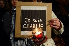 """A woman holds a candle and a poster reading """"Je suis Charlie"""" (I am Charlie) during a spontaneous vigil in front of the French embassy on January 7, 2015 in Berlin to express solidarity with employees of the French satirical weekly Charlie Hebdo that has been target of an attack by unknown gunmen. German Chancellor Angela Merkel condemned the """"despicable"""" attack on Charlie Hebdo that left at least 12 people dead in a condolence letter to President Francois Hollande.       AFP PHOTO / JOHN…"""
