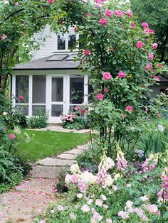 A cute, cottage-style entrance with a rose-covered arbor over a flagstone path. Foxgloves (Digitalis), pink primrose (Oenothera), and peonies add a soft, romantic feel up front, and a lush green lawn creates a welcoming carpet beyond.