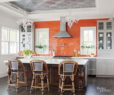 Two contrasting tiles -- tin and ceramic -- create an eclectic yet modern vibe in this energetic kitchen. Used as an accent, the orange tile offers a colorful contrast to what would otherwise be an overpoweringly white space. Tin tiles on the recessed ceiling lend the space a shimmering effect, offering a balance to the warm wood island and floor./