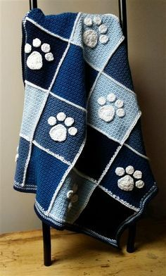"""This heirloom blanket is hand crocheted out of Acrylic yarn in a variety of blues....Pale, Ocean, Summer and Navy.  The adorable puppy paw prints are made with 100% white cotton and are individually made and stitched on with care.   <br/>The blanket measures at approx. 36""""X30"""" and is the ideal size for crib, cradle, carseat or stroller.  A wonderful shower gift idea!"""