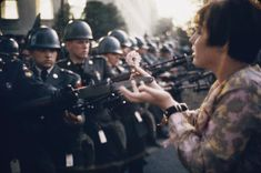 Jane Rose Kasmir plants a flower on the bayonets of guards at the Pentagon during a protest against the Vietnam War on October 21, 1967. The photograph would eventually become the symbol of the flower power movement.