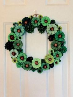 Hand painted pine cone wreath in shades of green. 13.5 x 13.5 diameter.