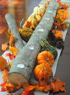 décoration de table automne - porte-bougies branche, citrouilles orange et vertes, pommes de pin et feuilles multicolores