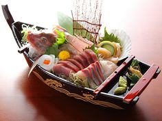 Sashimi Boat FUNAMORI. FUNAMORI is a type of sashimi arrangements. Several portions of sashimi and often a sea bream are arranged on a wooden boat like container. One characteristic of a funamori that you will notice is the big head of the fish. FUNAMORI is quite an expensive dish, which is usually served on special occasions. The boat container can add excitement to the banquet table, and since the boat is associated with fishermen, it can signify the freshness of the ingredients.