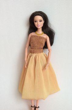 Dvoudílné šatičky Set pro Barbie se skládá z topu - minišatiček a sukně, která se zapíná na patentku. Doplňky - kruhový šál a korálky. Nevhodné pro děti do 3 let.