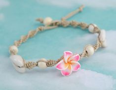 Macrame anklet made from natural hemp twine, two cowrie shells, wood beads and a pink polymer clay flower in the center. This anklet can be customized 1) Choose the length 2) Choose clasp style, bead and loop or loose ends to tie. ❀ **** ❀ **** ❀ Measuring Length Place a tape measure