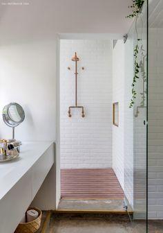 Banheiro com revestimento de subway tiles, chuveiro de cobre e deck de madeira.