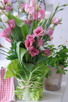 pinks in cabbage leaf-covered glass/vase...