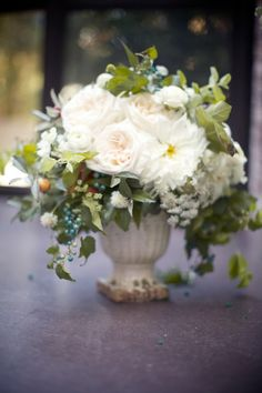 Ceramic urn with an abundance of white flowers and trailing greenery.