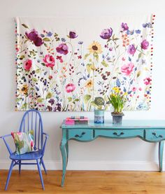 Easy wall decoration - a piece of pretty floral fabric w/a dowel and pom pom trim