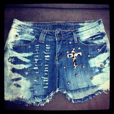 Shorts jeans com barra desfiada / cruz / rebites / oncinha