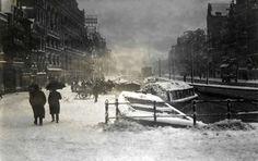Amsterdam in de winter/sfeerbeeld. Sneeuw in Amsterdam. Voetgangers in de sneeuw op het Rokin. Op de achtergrond zijn de sneeuwruimers bezig de verzamelde sneeuw in het water van het Rokin te storten. Foto 1916.
