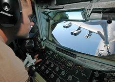 Boom operator of a KC-135 Stratotanker refuels a B-52 Stratofortress in flight.