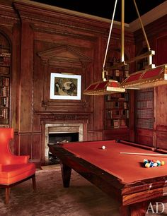 A Revitalized 1930s Mansion in Old Westbury, New York : Architectural Digest | A pool table by Blatt Billiards, an Art Deco light fixture, and a 1930s French oil painting strike perfect period notes in the paneled billiard room.