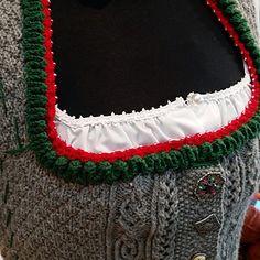 Verspielte Trachtenjacke mit Rüsche am Ausschnitt, Schößchen mit verkürzten Reihen und Rückenpasse mit Zugmaschenmuster. Die gehäkelte Rüsche am Ausschnitt und an den Ärmeln ist mir Perlen verziert. Das Zugmaschenmuster wird mit verschränkten und gekreuzte Maschen in jeder Reihe (Hin- und Rückreihe) gearbeitet