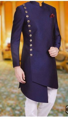 Flaunt your charm with extremely elegant navy blue side cut sherwani. The sherwani features magnificent buttons on one side with detailings and an exquisite pocket square that will make you look positively radiant. African Wear Styles For Men, African Dresses Men, African Clothing For Men, African Suits, African Shop, African Style, Indian Style, Indian Wear, Prom Suits For Men