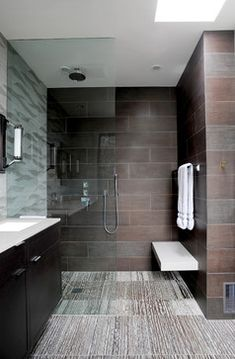 Contemporary bathroom with curbless shower floor  floating bench  floating vanity mounted to a tiled wall  and a full height fixed glass screen recessed into hidden channels  #bathroomdesign