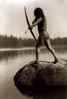 Historic image of a Bowman. It was taken in 1910 by Edward S. Curtis.    The image shows him standing on rock in water and aiming arrow.    Contact curator@old-picture.com.