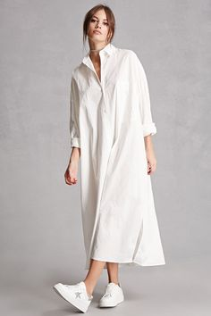 This longline cotton woven shirt dress features an oversized silhouette with dropped shoulders, a button-front placket, basic collar, chest patch pocket, long buttoned cuff sleeves, and a vented curved hem. This is an independent brand and not a Forever 21 branded item.