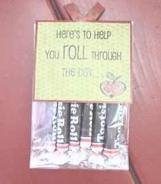 """6 Tootsie Rolls inside a cellophane bag with a tag that says:  """"Here's to help you roll through the day..."""""""