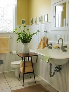 Cottage style bathroom with wall mounted sink, bright yellow walls and a hint of green with that fabulously unexpected pitcher arrangement.
