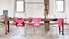 Wooden table with pink designer chairs. The chandelier is interesting too. Would work well outdoors as well.