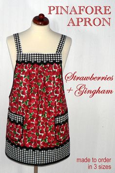 Lovely Strawberry Pinafore Apron (accented with black gingham) which is designed to be easy to put on and take off-- with no ties, buttons, or fasteners of any kind. (Originally designed for a friend with limited mobility.) Simply slip the apron over your head like a t-shirt and slide your arms into the generous openings to put it on. Apron rests totally on the shoulders, placing no strain on the neck. Comfortable enough to wear all day long! Apron fully covers your clothing for protection…