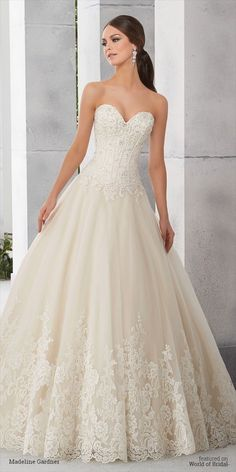 A strapless beaded boned alencon lace bodice with corset back on a full tulle ball gown with wide hem