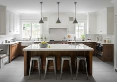 Tolix stools align at a brown wood kitchen island topped with a white quartz cou. Tolix stools align at a brown wood kitchen island topped with a white quartz countertop and a sink with a gooseneck faucet. Living Room Kitchen, Home Decor Kitchen, Kitchen Interior, Home Kitchens, Dream Kitchens, Wood Top Island Kitchen, Kitchen Islands, Brown Kitchens, Home And Deco