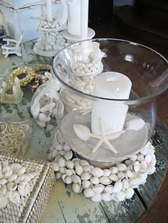 Some sand, sea shells, a candle and a glass vase creates this beach themed centerpiece.