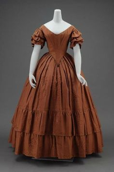 A brown silk faille dress with wide cut flaring neckline, short sleeves with two puffs and added embroidered cuff at end, boned fitted bodice ending in deep point center front, full skirt with fullness in pleats, large brown embroidered rose pattern over seams in front of skirt, two deep gathered flounces on skirt embroidered with same pattern, laced down center back of bodice; entire skirt lined with coarse sized cotton. American, c1840.