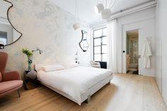 35 idee per arredare la camera da letto. La parete sopra la testiera del letto è lasciata libera e la decorazione è affidata alla coppia di specchi montati sopra i comodini e il wallpaper quasi impalpabile.