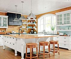 The Natural Beauty of knotty pine makes for a great background for a white kitchen. And I love the barstools!