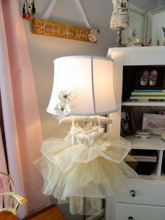 Dress hanging on padded hanger from regular floor lamp.