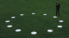 Ezequiel Montero Swinnen - Circumvolare Instalación - 12 relojes de pared dispuestos en forma de círculo sobre el piso, funcionando con una hora de diferencia exacta entre cada uno. 2011. Bisagra Arte Contemporaneo