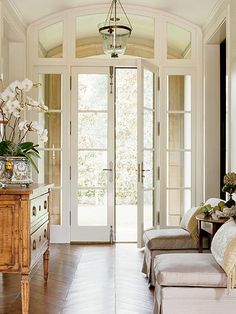 French doors embrace the outside vistas, in this case gardens, as part of this foyer's décor.