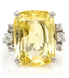 An Art Deco Platinum, Yellow Sapphire and Diamond Ring, containing one cushion cut yellow sapphire weighing approximately 12.25 carats and six old European cut diamonds weighing approximately 0.28 carat total. Stamp: PLAT.